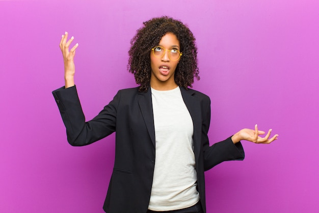 Młoda czarna kobieta wzrusza ramionami z głupim, szalonym, zmieszanym, zdziwionym wyrazem twarzy, czując się zirytowana i nieświadoma