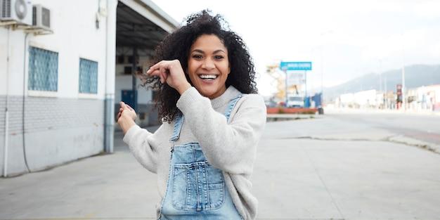 Młoda czarna kobieta z afro włosów śmiejąc się i ciesząc