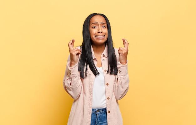 Młoda czarna kobieta z niepokojem krzyżuje palce i liczy na szczęście ze zmartwionym spojrzeniem