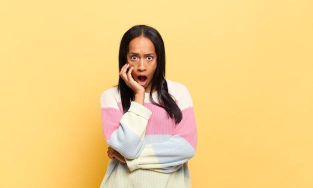 Młoda czarna kobieta z otwartymi ustami w szoku i niedowierzaniu, z ręką na policzku i skrzyżowanymi ramionami, czując się oszołomiona i zdumiona