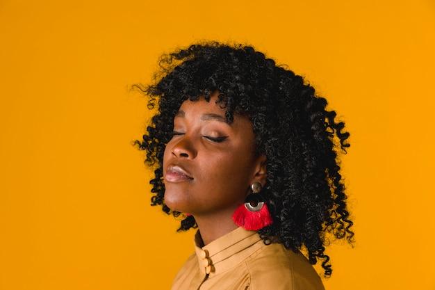 Młoda czarna kobieta z pochyloną głową i zamkniętymi oczami