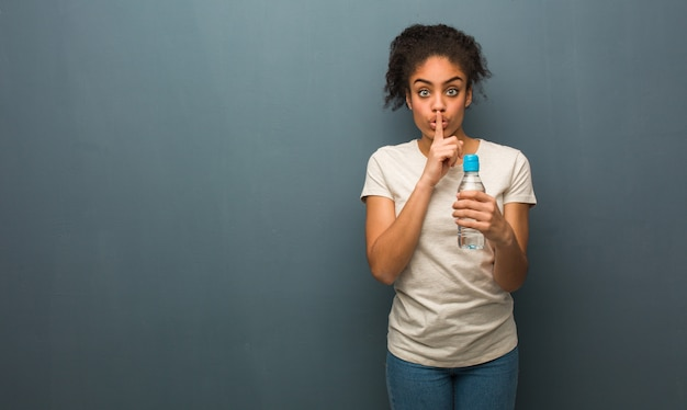 Młoda czarna kobieta zachowuje tajemnicę lub prosi o ciszę. trzyma butelkę wody.