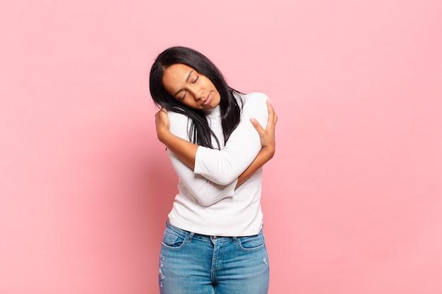 Młoda czarna kobieta zakochana, uśmiechnięta, przytulająca się i obejmująca siebie, pozostająca samotna, samolubna i egocentryczna