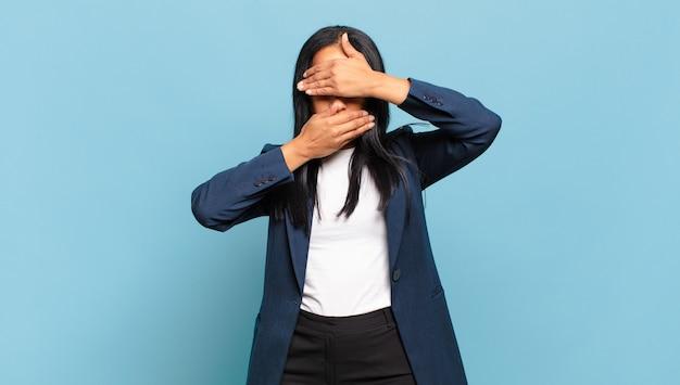 """Młoda czarna kobieta zakrywająca twarz obiema rękami mówiąca """"nie"""" do kamery! odmawianie zdjęć lub zabranianie zdjęć. pomysł na biznes"""
