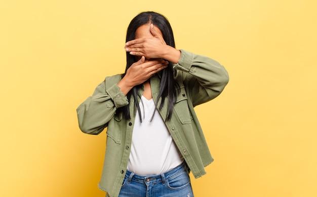 """Młoda czarna kobieta zakrywająca twarz obiema rękami mówiąca """"nie"""" do kamery! odmowa robienia zdjęć lub zabranianie zdjęć"""