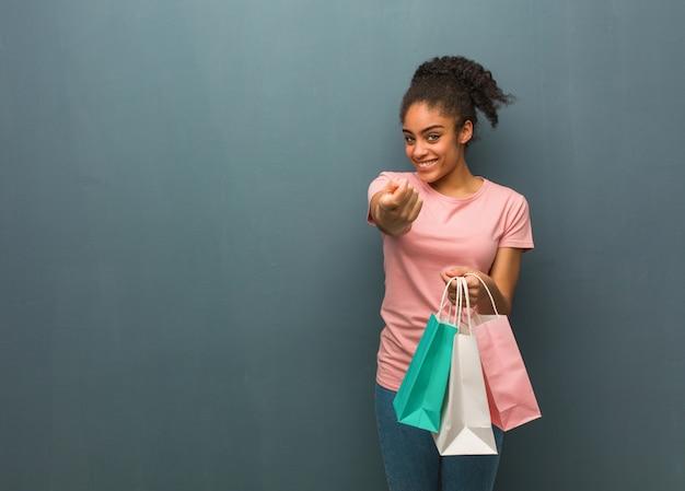 Młoda czarna kobieta zaprasza. ona trzyma torby na zakupy.