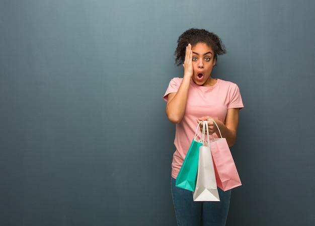 Młoda czarna kobieta zaskoczona i zszokowana ona trzyma torby na zakupy