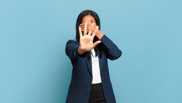 Młoda czarna kobieta zasłaniając twarz ręką i kładąc drugą rękę do przodu, aby zatrzymać aparat, odmawiając zdjęć lub zdjęć. pomysł na biznes