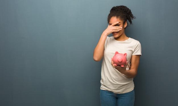 Młoda czarna kobieta zawstydzona i jednocześnie śmiejąca się. trzyma skarbonkę.