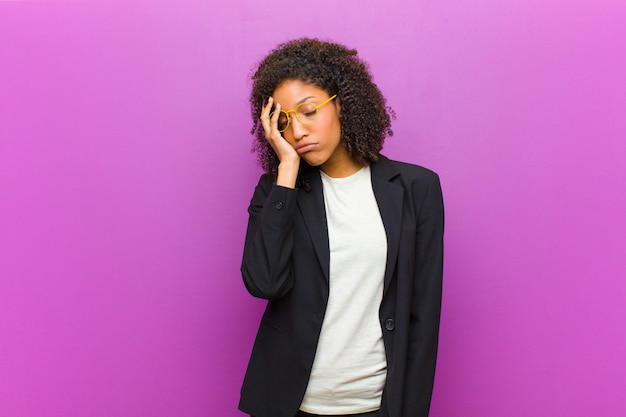 Młoda czarna kobieta znudzona, sfrustrowana i senna po męczącym, nudnym i żmudnym zadaniu, trzymając twarz ręką