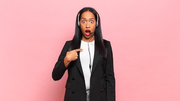 Młoda czarna kobieta zszokowana i zaskoczona, z szeroko otwartymi ustami, wskazująca na siebie. koncepcja telemarketingu