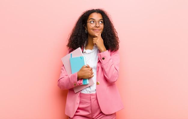 Młoda czarna ładna biznesowa kobieta z książkami przeciw menchii ściany ścianie