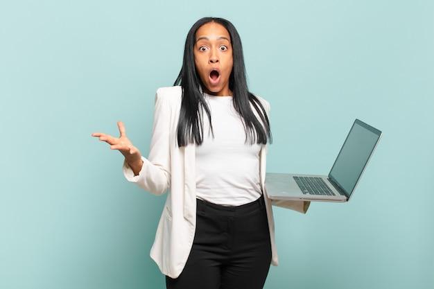 Młoda czarnoskóra kobieta bardzo zszokowana i zaskoczona, niespokojna i spanikowana, o zestresowanym i przerażonym spojrzeniu. koncepcja laptopa