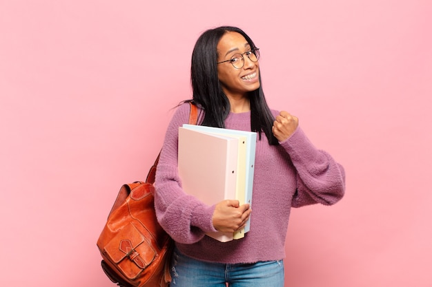 Młoda czarnoskóra kobieta czuje się szczęśliwa, pozytywna i odnosząca sukcesy, zmotywowana, gdy staje przed wyzwaniem lub świętuje dobre wyniki. koncepcja studenta