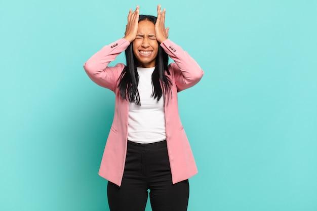Młoda czarnoskóra kobieta czuje się zestresowana i niespokojna, przygnębiona i sfrustrowana z bólem głowy, podnosząc obie ręce do głowy. pomysł na biznes