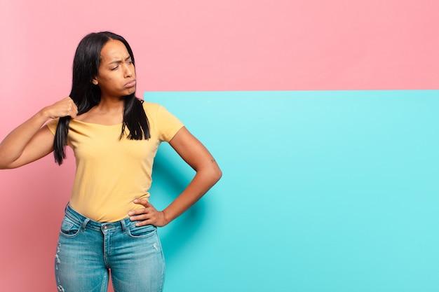 Młoda czarnoskóra kobieta czuje się zestresowana, niespokojna, zmęczona i sfrustrowana, ciągnie za szyję koszuli, wygląda na sfrustrowaną problemem. kopia koncepcja przestrzeni