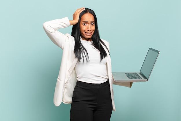 Młoda czarnoskóra kobieta czuje się zestresowana, zmartwiona, niespokojna lub przestraszona, z rękami na głowie, panikując z powodu błędu. koncepcja laptopa