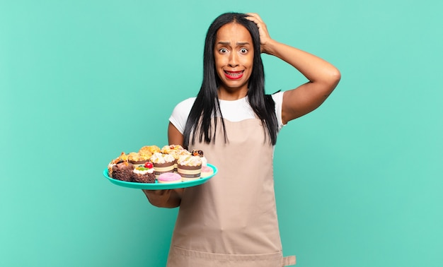 Młoda czarnoskóra kobieta czuje się zestresowana, zmartwiona, niespokojna lub przestraszona, z rękami na głowie, panikująca z powodu błędu. koncepcja szefa kuchni piekarni