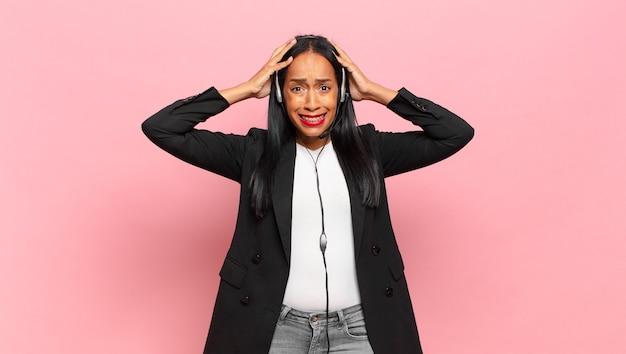 Młoda czarnoskóra kobieta czuje się zestresowana, zmartwiona, niespokojna lub przestraszona, z rękami na głowie, panikująca z powodu błędu. koncepcja telemarketingu