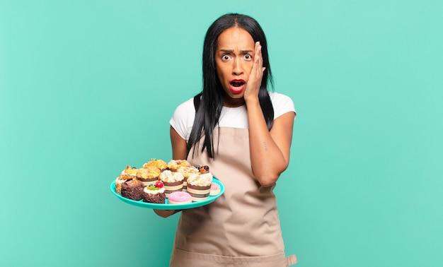 Młoda czarnoskóra kobieta czuje się zszokowana i przestraszona, wygląda na przerażoną z otwartymi ustami i dłońmi na policzkach. koncepcja szefa kuchni piekarni