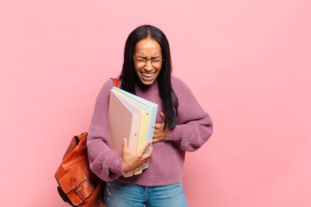 Młoda czarnoskóra kobieta śmiejąca się głośno z jakiegoś zabawnego żartu, szczęśliwa i wesoła, dobrze się bawi