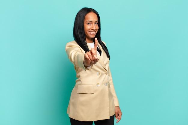 Młoda czarnoskóra kobieta, uśmiechnięta dumnie i pewnie, triumfalnie tworząca pozę numer jeden, czując się jak przywódczyni. pomysł na biznes