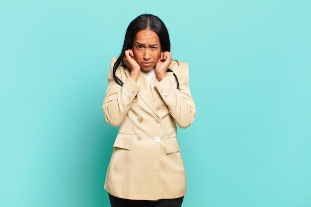 Młoda czarnoskóra kobieta wyglądająca na rozgniewaną, zestresowaną i zirytowaną, zasłaniając obydwoje uszu ogłuszającym hałasem, dźwiękiem lub głośną muzyką. pomysł na biznes