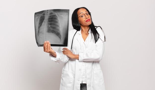 Młoda czarnoskóra kobieta wzrusza ramionami, czuje się zdezorientowana i niepewna, wątpi ze skrzyżowanymi rękami i zdziwionym spojrzeniem. koncepcja lekarza