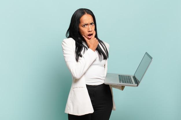 Młoda czarnoskóra kobieta z szeroko otwartymi ustami i oczami iz ręką na brodzie, czując się nieprzyjemnie zszokowana, mówiąc co lub wow. koncepcja laptopa