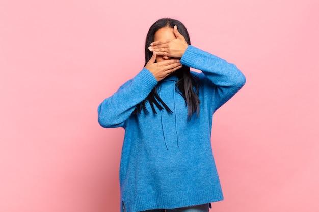 """Młoda czarnoskóra kobieta zakrywająca twarz obiema rękami mówiąca """"nie"""" do aparatu, odmawiająca robienia zdjęć lub zabraniająca robienia zdjęć"""