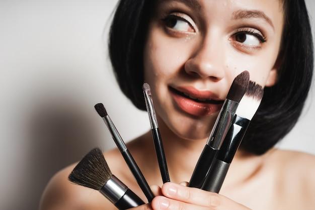 Młoda czarnowłosa dziewczyna trzymająca pędzle do makijażu, patrząca w lewo z zainteresowaniem, uśmiechnięta. na białym tle