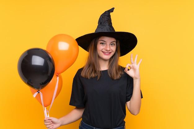 Młoda czarownica gospodarstwa czarne i pomarańczowe balony na imprezy halloween pokazano ok znak palcami