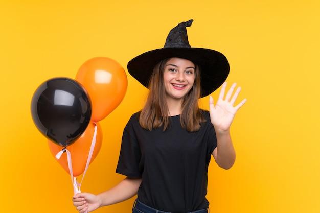 Młoda czarownica trzyma czarne i pomarańczowe balony na imprezy halloween pozdrawiając ręką z happy wypowiedzi