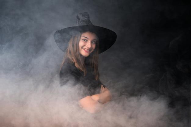 Młoda czarownica trzyma czarne i pomarańczowe balony na imprezy halloween