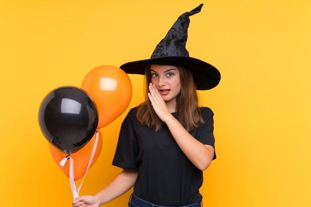 Młoda czarownica trzyma czarne i pomarańczowe balony na imprezy halloweenowe, szepcząc coś