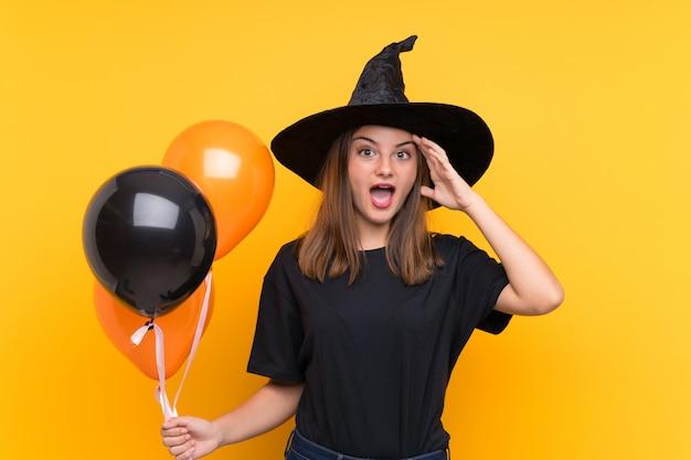 Młoda czarownica trzyma czarne i pomarańczowe balony na przyjęcia z zaskoczeniem i zszokowanym wyrazem twarzy