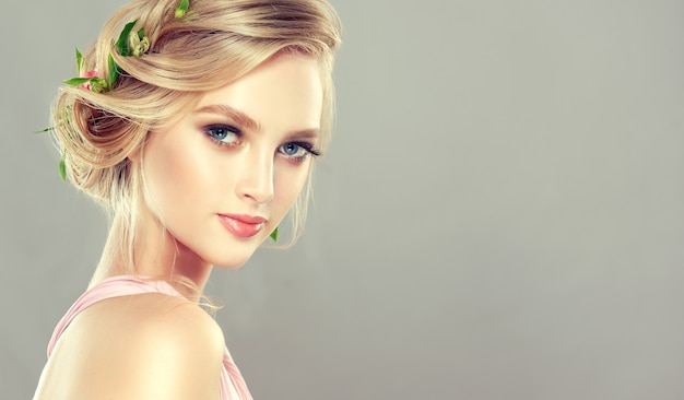 Młoda, czarująca modelka o niebieskich oczach i blond włosach zebranych w elegancką fryzurę w świeże kwiaty. sztuka fryzjerska, koloryzacja włosów i kosmetyki.
