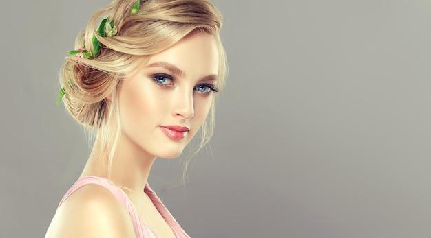 Młoda, czarująca, niebieskooka modelka o blond włosach zebranych w elegancką fryzurę ze świeżymi kwiatami. sztuka fryzjerska, koloryzacja włosów, kosmetyki i kosmetyki.