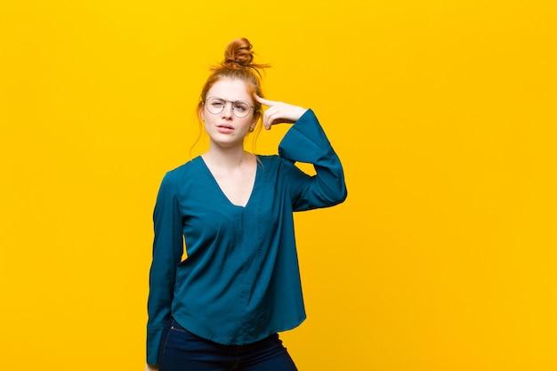 Młoda czerwona głowa czuje się zmieszana i zdziwiona, pokazując, że jesteś szalona, szalona lub oszalała na punkcie pomarańczowej ściany