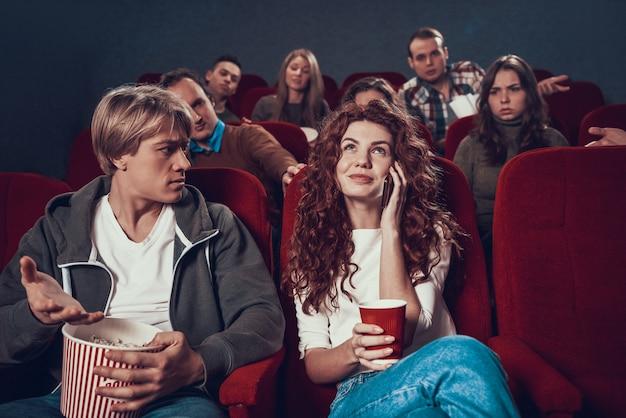 Młoda czerwona głowa dziewczyna mówi przez telefon podczas pokazu filmowego.