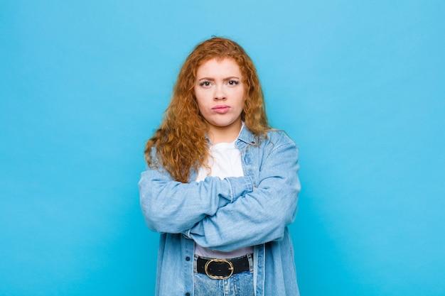 Młoda czerwona głowa kobieta czuje się niezadowolona i rozczarowana, wygląda poważnie, zirytowana i wściekła ze skrzyżowanymi rękami na niebieskiej ścianie