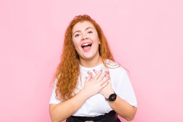 Młoda czerwona głowa kobieta czuje się romantycznie, szczęśliwa i zakochana, uśmiecha się wesoło i trzyma ręce blisko serca na tle różowej ściany