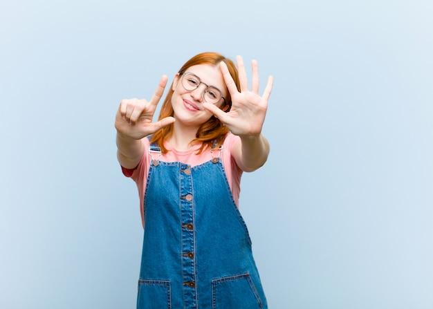 Młoda czerwona głowa kobieta uśmiechnięta i wyglądająca przyjaźnie, pokazując numer siedem lub siódmy z ręką do przodu, odliczając