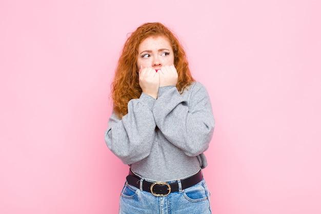 Młoda czerwona głowa kobieta wygląda na zmartwioną, niespokojną, zestresowaną i przestraszoną, gryzie paznokcie i szuka bocznej kopii przestrzeni na różowej ścianie