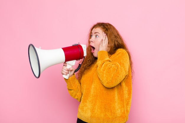 Młoda czerwona głowa kobiety czuje się szczęśliwa, podekscytowana i zaskoczona, patrząc w bok obiema rękami na twarzy z megafonem