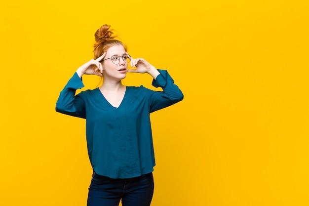 Młoda czerwona głowa kobiety czuje się zdezorientowana lub wątpiąca, koncentruje się na pomyśle, mocno myśli, chce skopiować miejsce na boku na pomarańczową ścianę