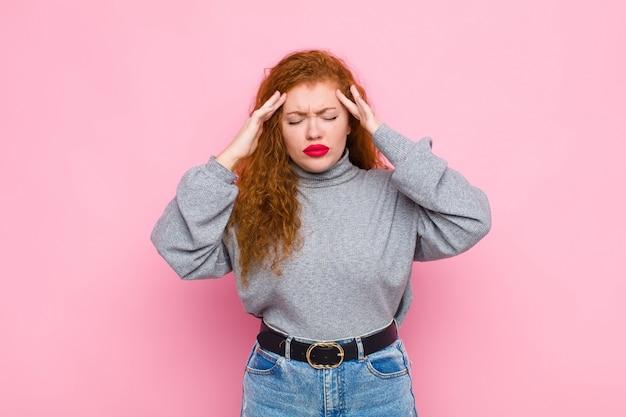 Młoda czerwona głowa kobiety patrząc zestresowany i sfrustrowany
