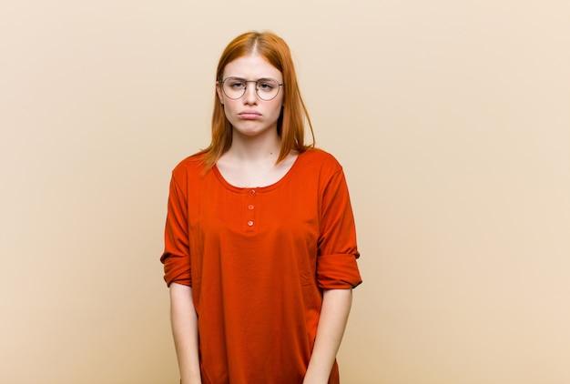 Młoda czerwona głowa ładna kobieta czuje się smutna i zestresowana, zdenerwowana z powodu złej niespodzianki, z negatywnym, niespokojnym spojrzeniem