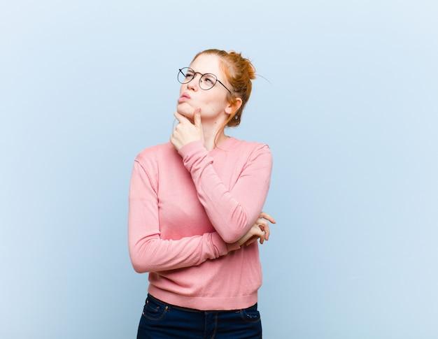 Młoda czerwona głowa ładna kobieta myśli, czując się niepewnie i zdezorientowana, z różnymi opcjami, zastanawiając się, jaką decyzję podjąć