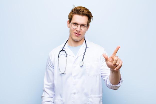 Młoda czerwona lekarka uśmiecha się i wygląda przyjaźnie, pokazuje numer dwa lub drugie ręką do przodu, odliczając